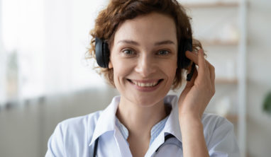 Smiling female doctor wearing headset looking at camera. Remote online medical chat consultation, telemedicine distance services, virtual physician conference call concept. Head shot close up portrait